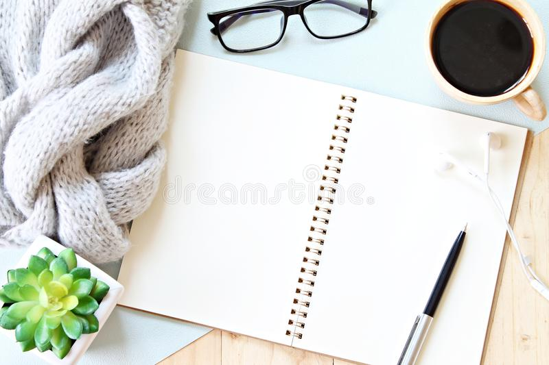 Flat lay or top view of gray knitted scarf, open blank notebook paper, coffee cup and eyeglasses on wooden background royalty free stock images