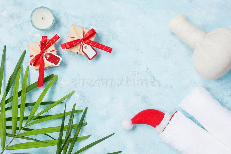 Flat lay top view holiday spa background: thai massage bag, towels and gift boxes on blue background royalty free stock photography
