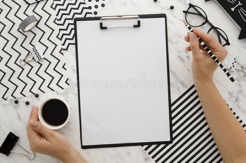 Woman hands hold pencil and coffee. Zebra background with blank clipboard and office accessories. Abstract Diagonal. Flat lay, top view Home office desk stock images