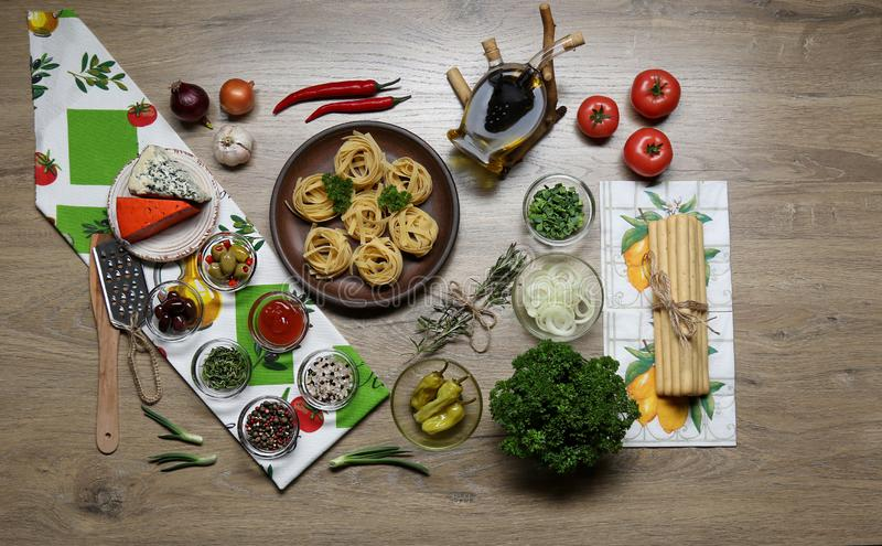 Flat lay, top view on the ingredients for cooking pasta on the background of a  table stock photography