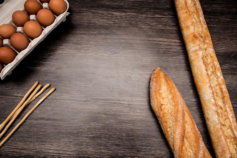 Flat lay top view of loaves of bread, sticks of bread an dozen of eggs. Flat lay top view of loaves of bread, grisinni bread sticks an dozen of eggs. Copy space royalty free stock photos