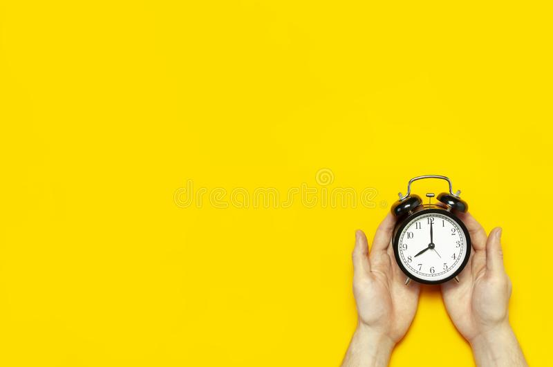 Flat lay top view male hand holding black vintage alarm clock on bright yellow color background with copy space. Creative Time stock photos