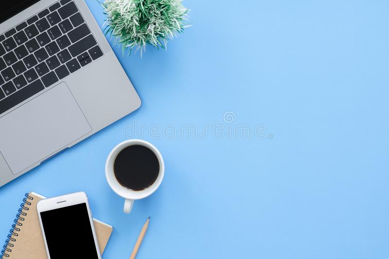 Flat lay top view mockup photo of working space with laptop, smartphone, coffee up and notebook on blue pastel background. stock image