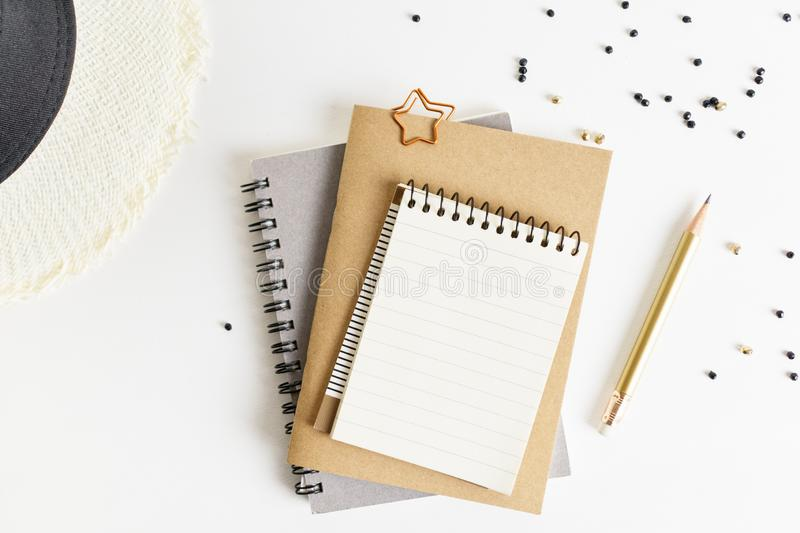 Flat lay top view notepad mockup: pencils, black beads, straw hat on white background. Clean and bright royalty free stock images