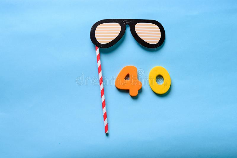 Flat lay top view number and sunglasses cute paper carnival mask. 40 celebrating yellow number with sunglasses cute paper mask on straw stick . Forty Modern royalty free stock image