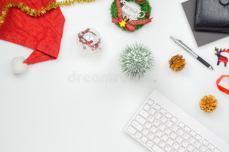 Flat lay top view office table desk, Christmas workspace with keyboard, Santa Claus hat and christmas decorations on white. Background, business, celebration stock photo