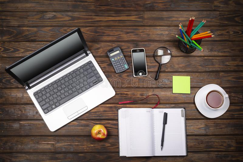 Concept freelancing, business concept, office table desk, laptop, empty notebook, cup of coffee, smartphone, calculator, wooden ba royalty free stock image