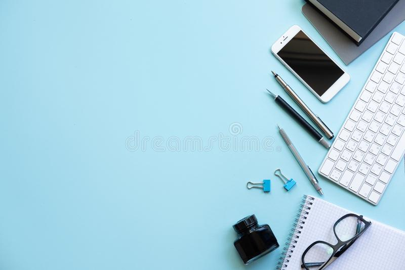 Flat lay, top view office table desk. Workspace with blank note book, keyboard, Blue office supplies on blue background. royalty free stock photos