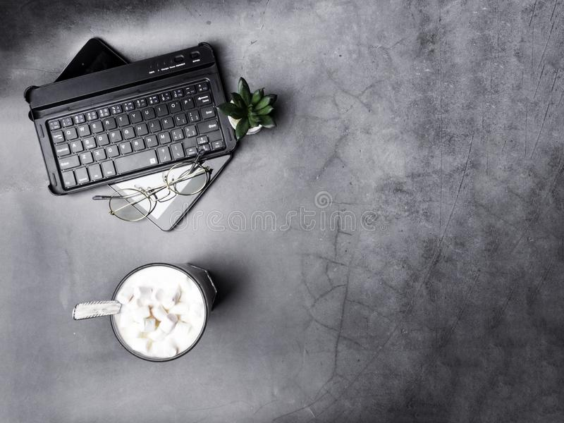 Flat lay, top view office table desk. Workspace, keyboard, glasses, green cactus, and coffee cup on grey background royalty free stock photography