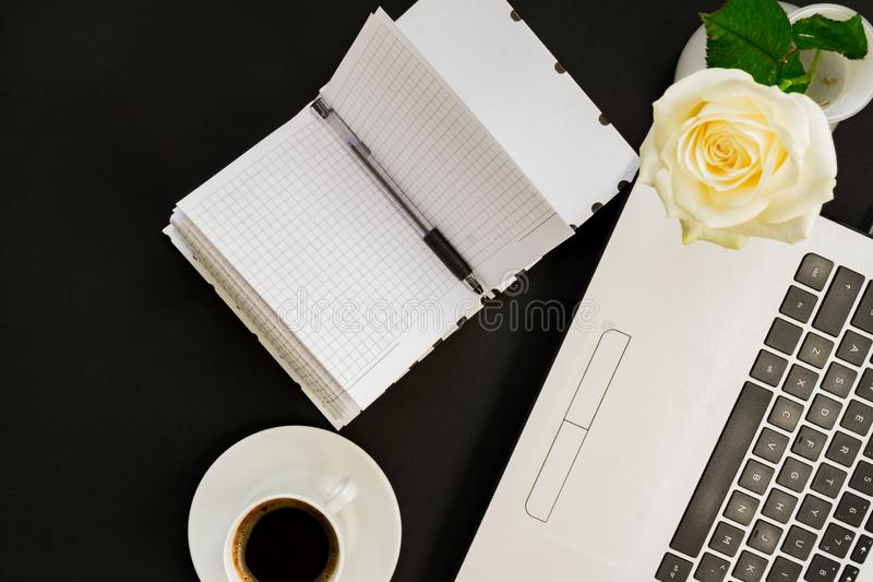 Flat lay, top view office table desk. Workspace with laptop, white rose, open diary and coffee mug on black background stock images