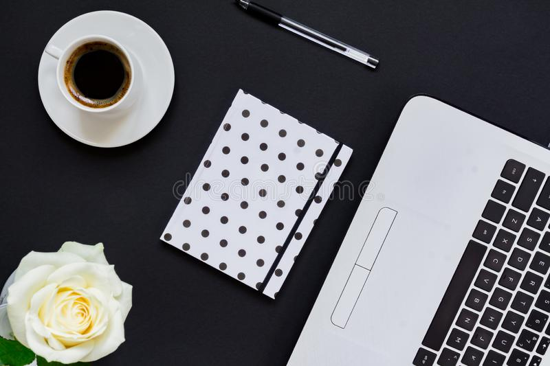 Flat lay, top view office table desk. Workspace with laptop, white rose, polka dot diary and coffee mug on black background stock photography
