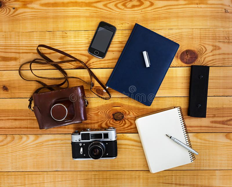 Flat lay, top view office table desk. Desk workspace with retro camera, diary, pen, case on wooden background royalty free stock photo
