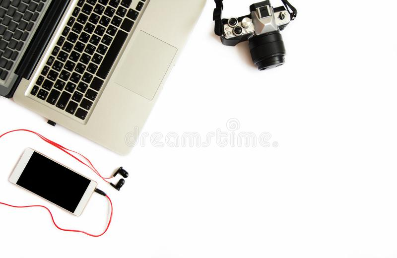 Flat lay top view photo of photographer working space with laptop, photo gear and phone with earphones on white background. Place stock image