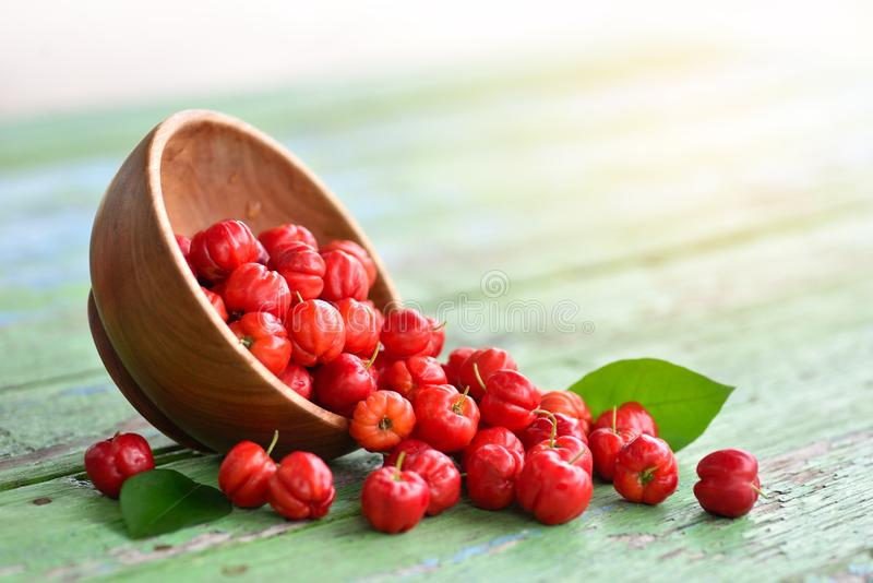 Flat lay top view Red Acerola Cherry in wooden bowl royalty free stock photos