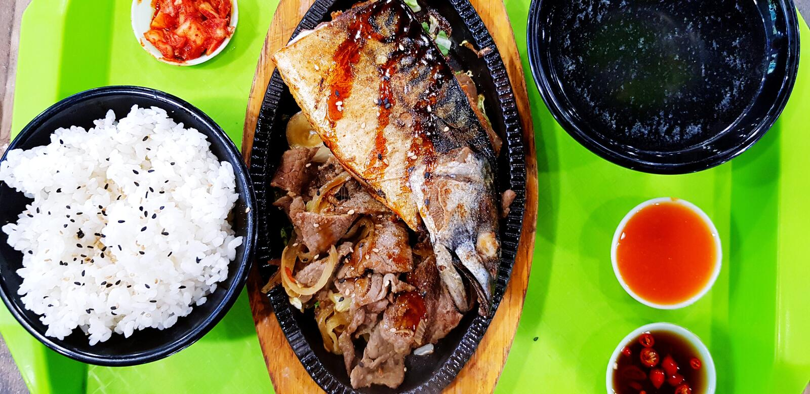 Flat lay or top view Saba and fried onion with teriyaki sauce with white rice and black bowl of soup on the green table at canteen stock photo