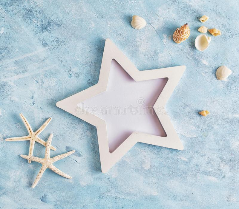 Flat lay top view Summer vacation mockup: star shaped photo frame, seashells and white starfish on blue background. Travel, beach royalty free stock photos