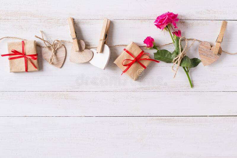 Flat lay, top view Valentines Day background with twine, wooden hears, rose, gifts royalty free stock image