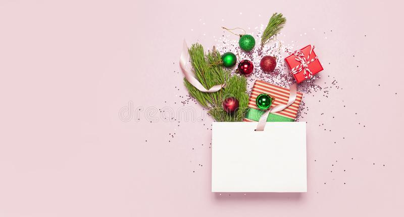 Flat lay top view White gift bag holographic glitter confetti red green christmas balls pine branches gift boxes on pink stock images