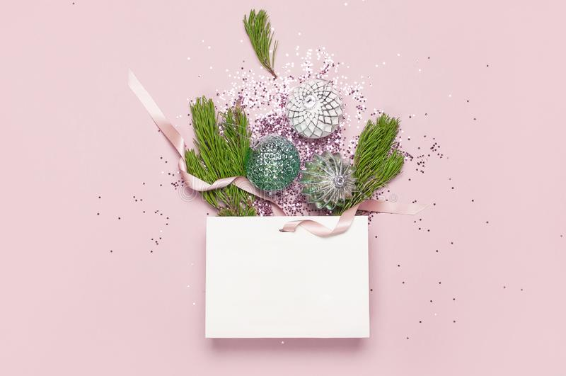 Flat lay top view White gift bag holographic glitter confetti Vintage Christmas New Year balls green pine branches on pink royalty free stock photo