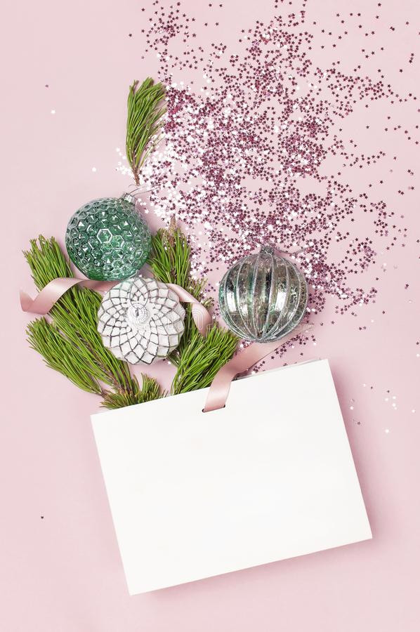 Flat lay top view White gift bag holographic glitter confetti Vintage Christmas New Year balls green pine branches on pink stock photography