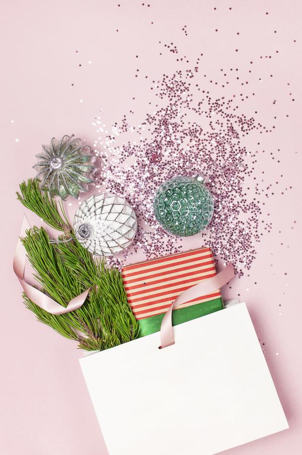 Flat lay top view White gift bag holographic glitter confetti Vintage Christmas New Year balls pine branches gift boxes on pink. Background Greeting card stock images