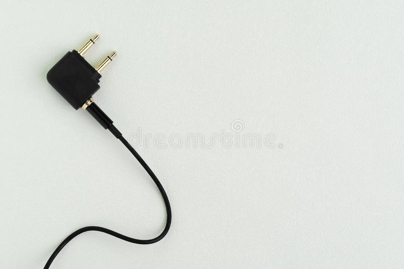 Flat lay of topview of headphone audio jack with 2 legs and black cable using in airplane, preparing for travel and tourist stock images