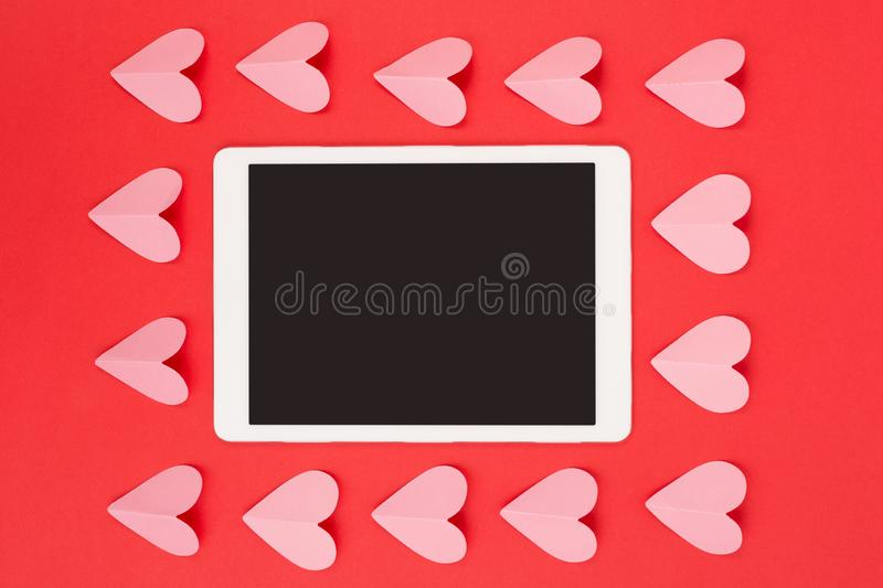 Flat lay of touchpad with blank screen on red background with paper cut hearts royalty free stock images