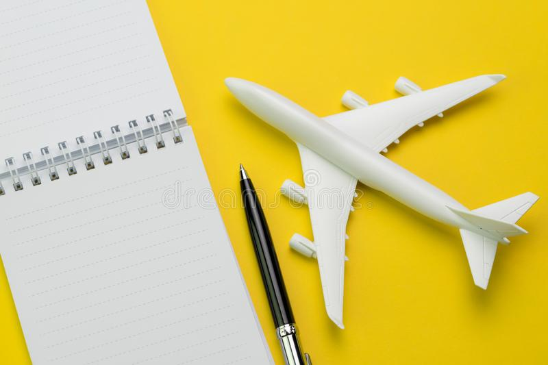 Flat lay of toy airplane with pen and white clean paper notepad. On vivid yellow background, travel destination wishlist or planning, holiday and vacation trip stock photography