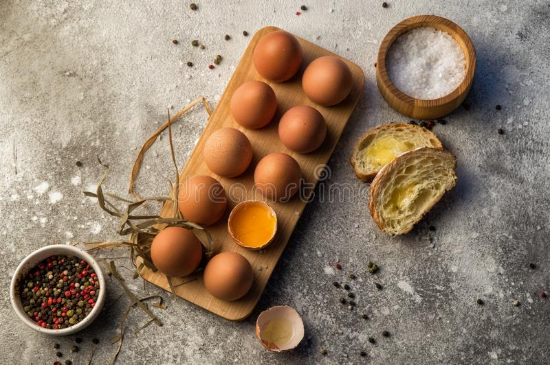 Flat lay. Traditional breakfast. A dozen farm eggs in a wooden tray, next to chunks of baguette with cheese and spices. Copy space stock image
