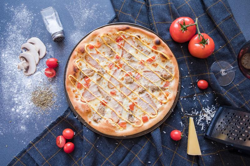 Flat lay with traditional Italian pizza with chiken, ham, pepper, cheese and tomatoes on dark blue stone table and  ingredients stock images