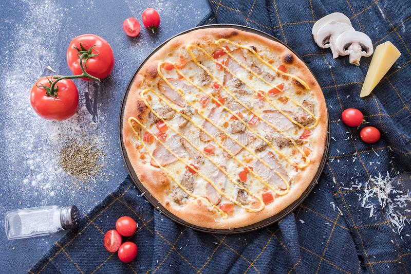 Flat lay with traditional Italian pizza with chiken, ham, pepper, cheese and tomatoes on dark blue stone table and  ingredients stock photography