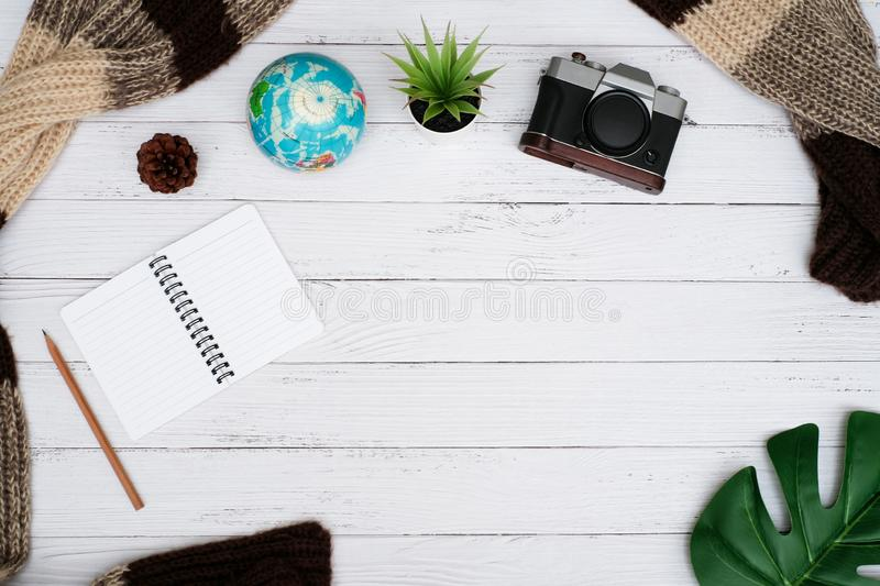Flat lay travel concept with white wooden background. Flat lay travel concept on white wooden background with accessory and equipment, blank notepad and leaves stock photo