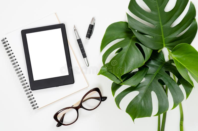 Flat lay tropical jungle Monstera leaves, paper notebook, e-book reader, glasses on white background. Top view feminine diary,. Stationery and electronic device royalty free stock photography