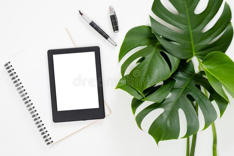 Flat lay tropical jungle Monstera leaves, paper notebook, e-book reader on white background. Top view feminine diary, stationery. And electronic device on home stock photos