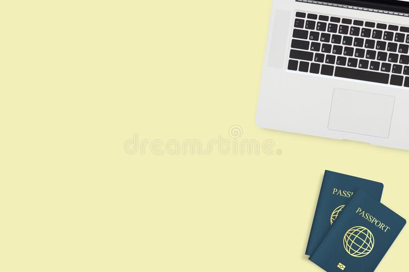 Flat lay of two passport computer laptop on pastel yellow stock photography