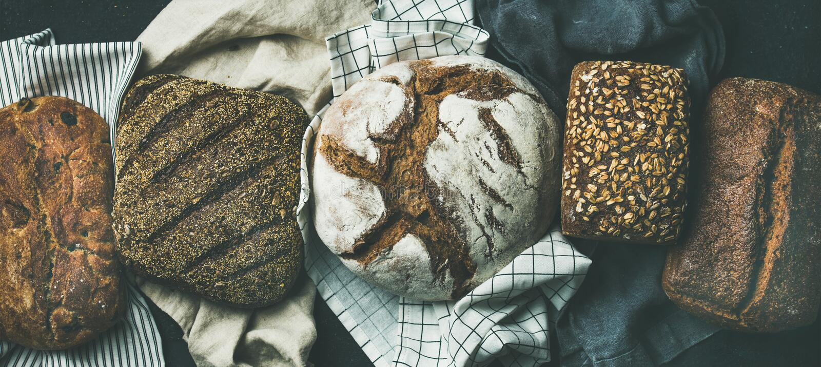 Flat-lay of Various bread selection loaves, black background stock images