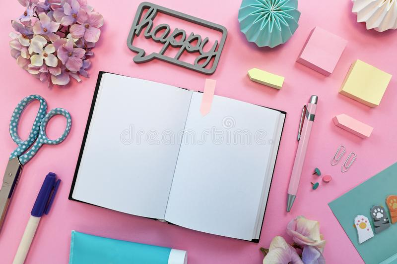 Flat lay with various colorful office supplies like pencils, scissors, notepads, pins and open empty notebook stock image