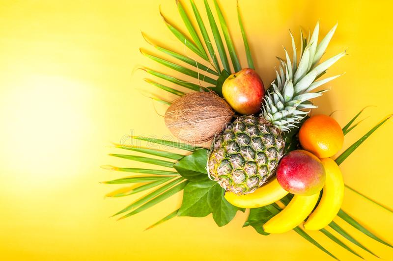Flat lay of various tropical fruits on palm leaves. Pineapple, m stock photography