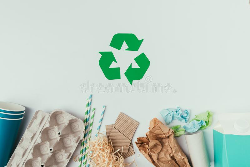 Flat lay with various types of garbage and recycle sign. Isolated on grey royalty free stock image
