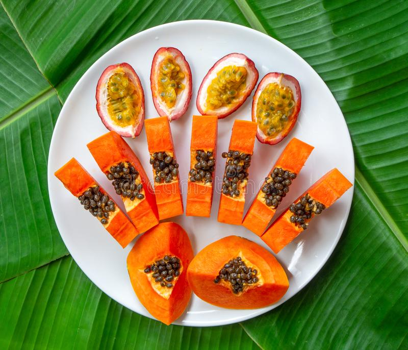 Flat lay. Vegetarian nutrition. papaya pieces and passion fruit on white plate with green banana leaves background, top view. Flat lay. Vegetarian nutrition royalty free stock photos