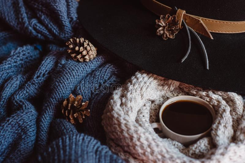 Flat lay view of autumn leaves and tartan textured blue sweater on white background with cup of coffee, glasses and a hat stock photos