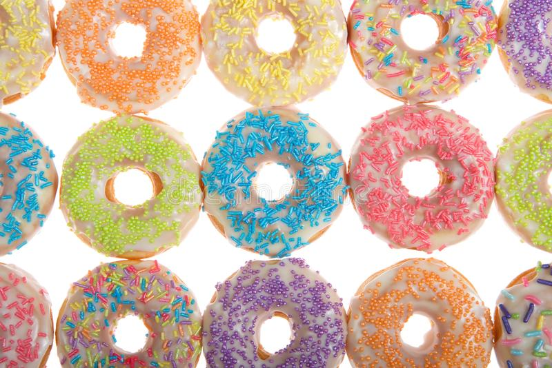 Close up on colorful sprinkle donuts isolated on white royalty free stock photo