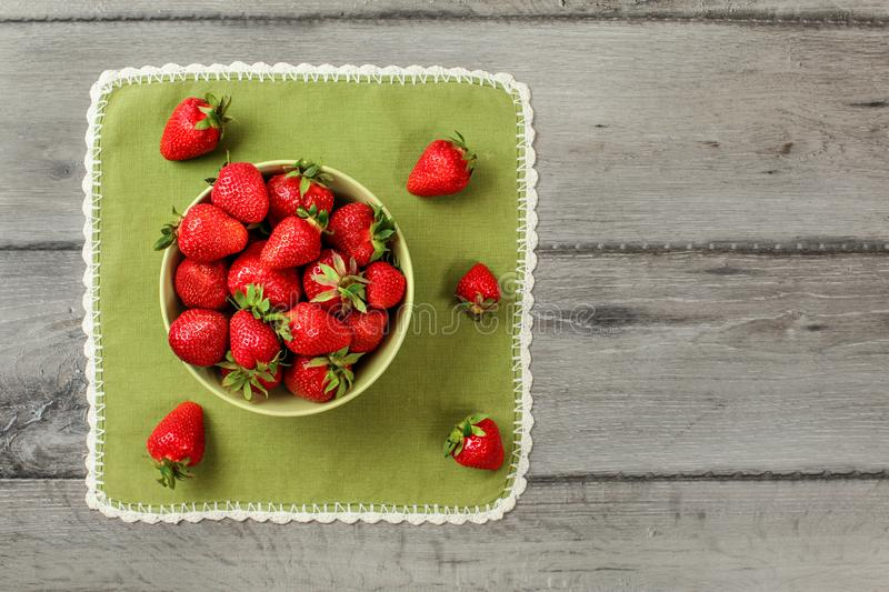 Flat lay view - small bowl with strawberries, some spilled on green tablecloth, gray wood desk under.  royalty free stock image