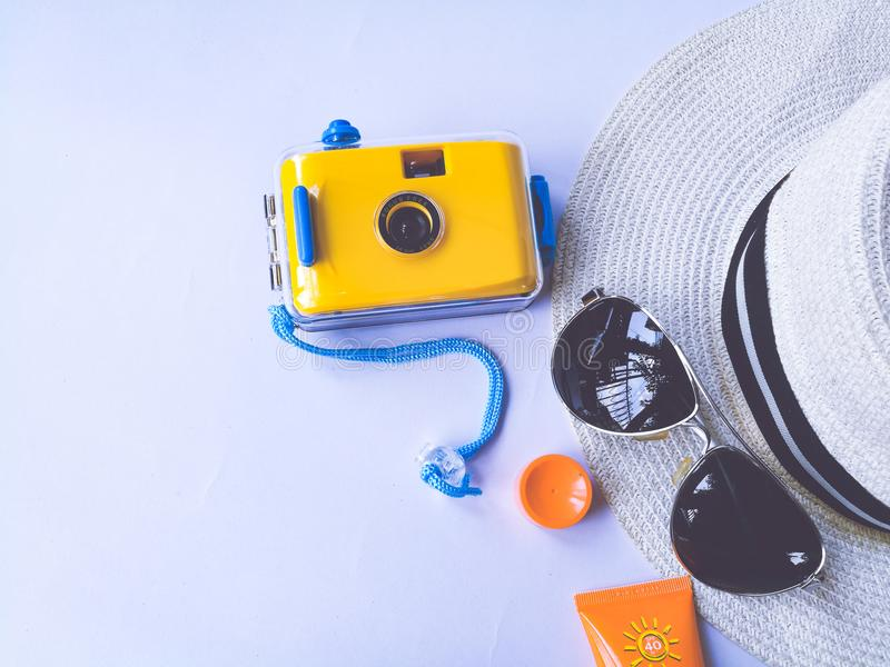 Flat lay view of summer and travel accessories. Waterproof yellow camera, Hat, sun glasses, sunblock cream protection. stock photography