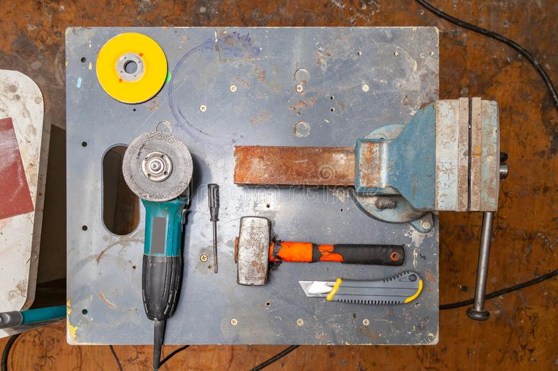 Flat lay view of a workbench with a set of tools consisting of a large heavy vise, angle grinder, screwdriver, cutter,. Sledgehammer, and a spare cutting disc royalty free stock photo