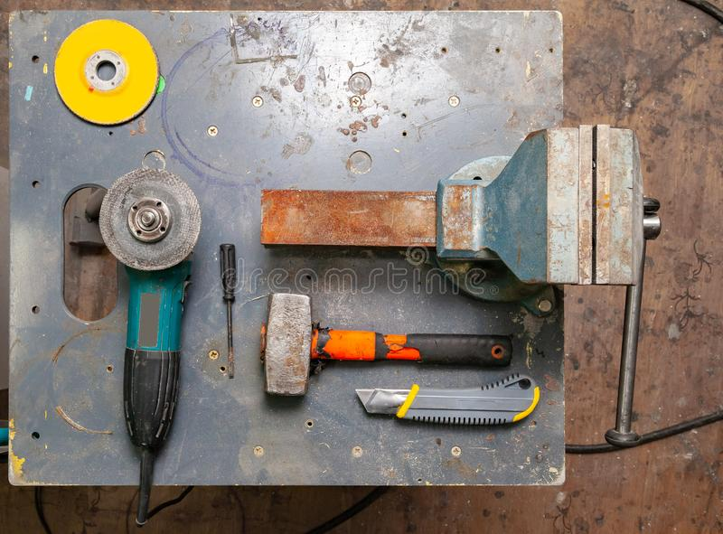 Flat lay view of a workbench with a set of tools consisting of a large heavy vise, angle grinder, screwdriver, cutter,. Sledgehammer, and a spare cutting disc stock photos