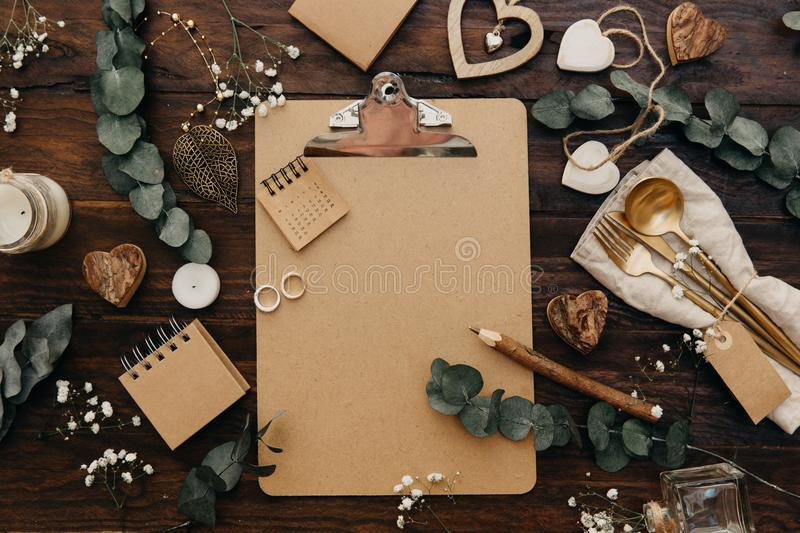 Flat lay Wedding planning. Craft clipboard with rustic decorations on wooden background royalty free stock photography
