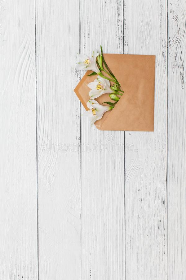 Flat lay with White lilies in craft envelope on old white wooden background royalty free stock photos