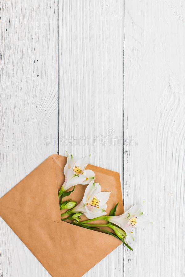 Flat lay with White lilies in craft envelope on old white wooden background royalty free stock photography