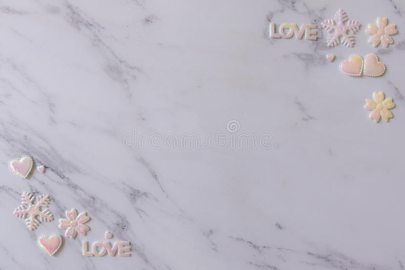 Flat lay of white marble background decorates with shining pink white pearl of hearts, letter of LOVE, snowflakes, and flowers stock photography